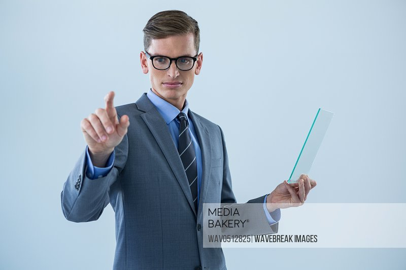 Businessman holding a glass sheet and touching an invisible screen against white background