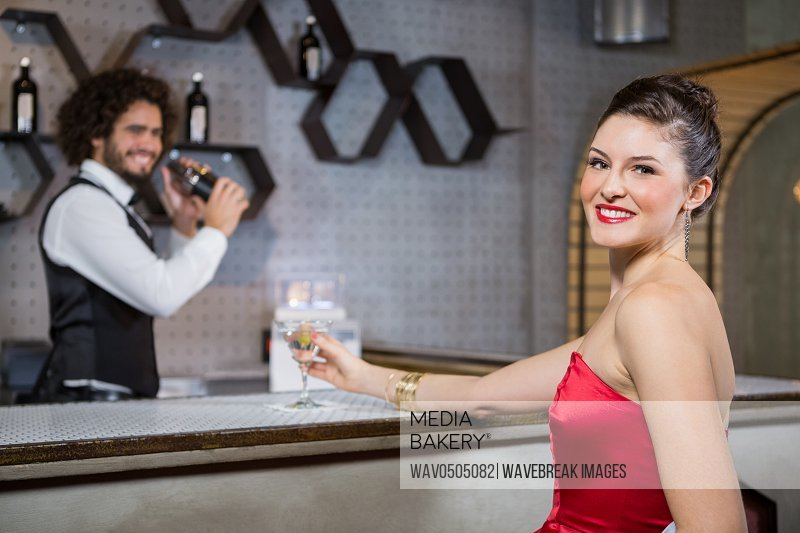 Portrait of smiling beautiful woman standing at bar counter in bar