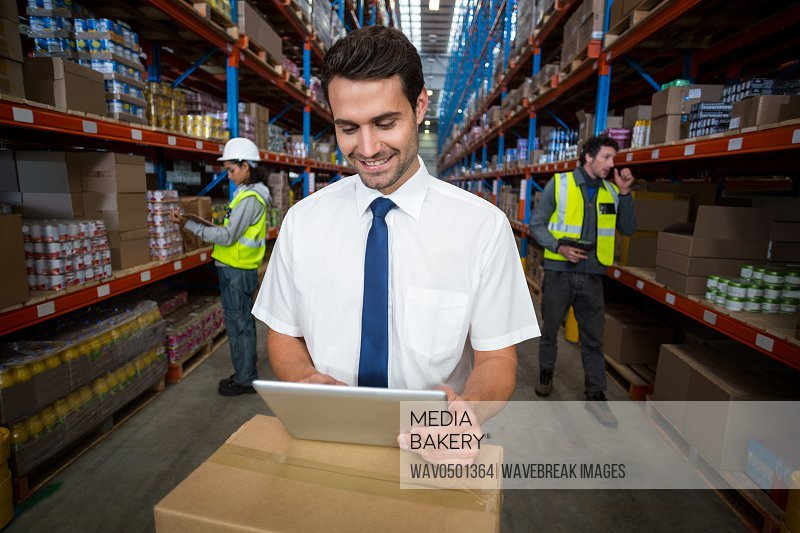 Warehouse manager using digital tablet in warehouse
