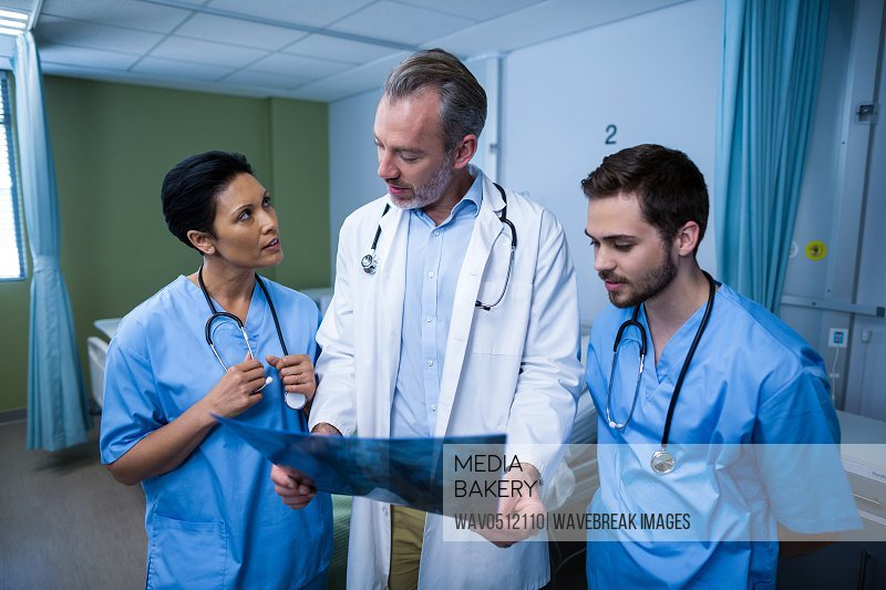 Doctor and nurse discussing x-ray during visit in ward