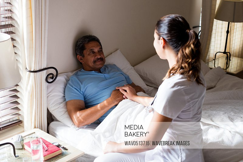 Female doctor interacting with senior patient in bedroom