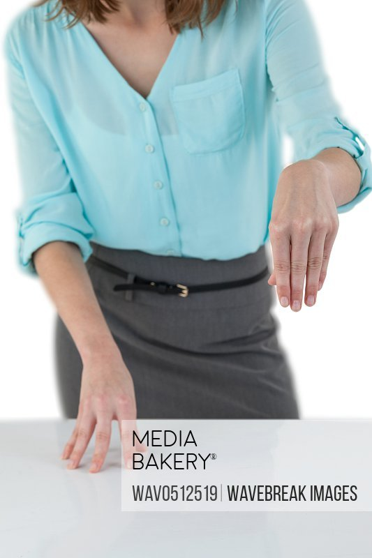 Mid section of business woman standing at table against white background