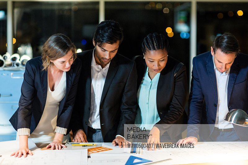 Group of businesspeople looking at the document in the office