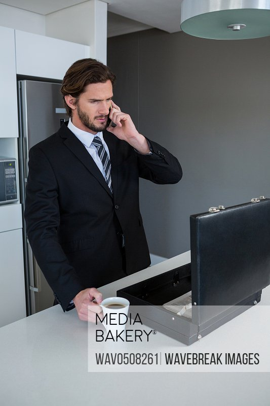 Businessman talking on mobile phone in kitchen at home