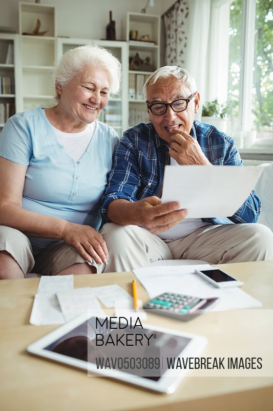 Senior couple interacting while checking the bills at home
