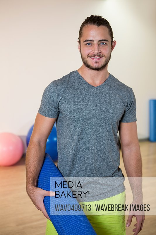 Portrait of smiling man holding rolled exercise mat in fitness studio