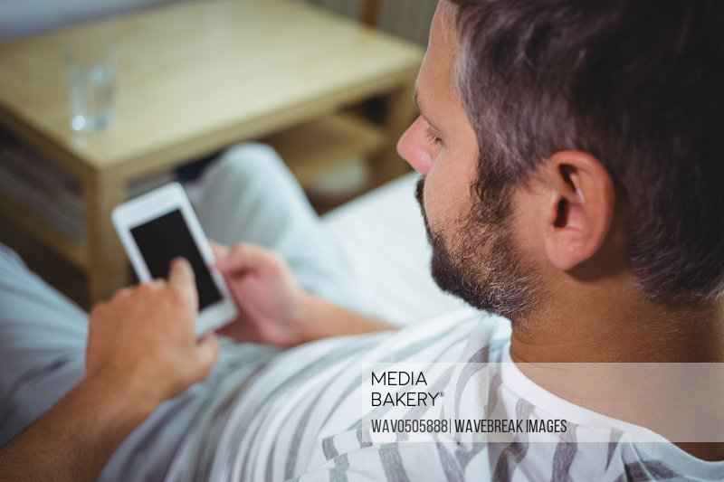 Man sitting on sofa and checking his mobile phone at home