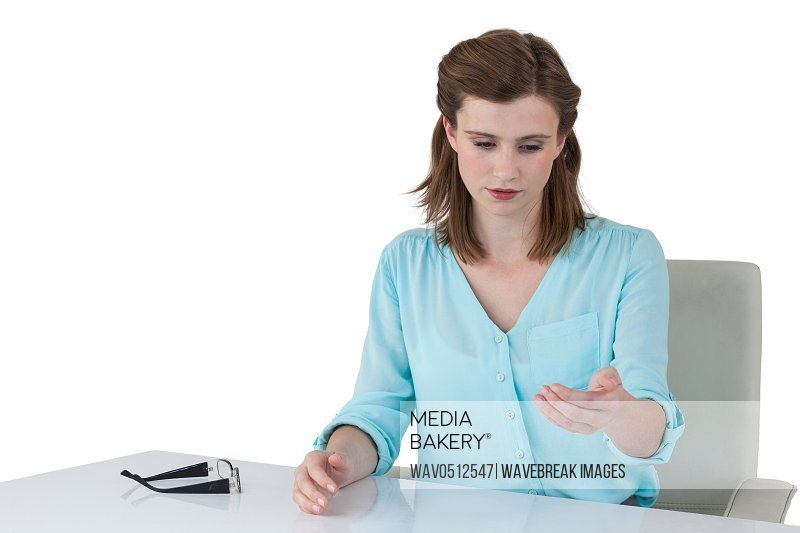 Businesswoman sitting at desk and using digital screen against white background