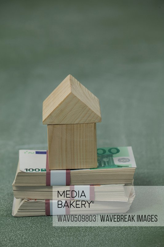 Model house on a pile of money against green background