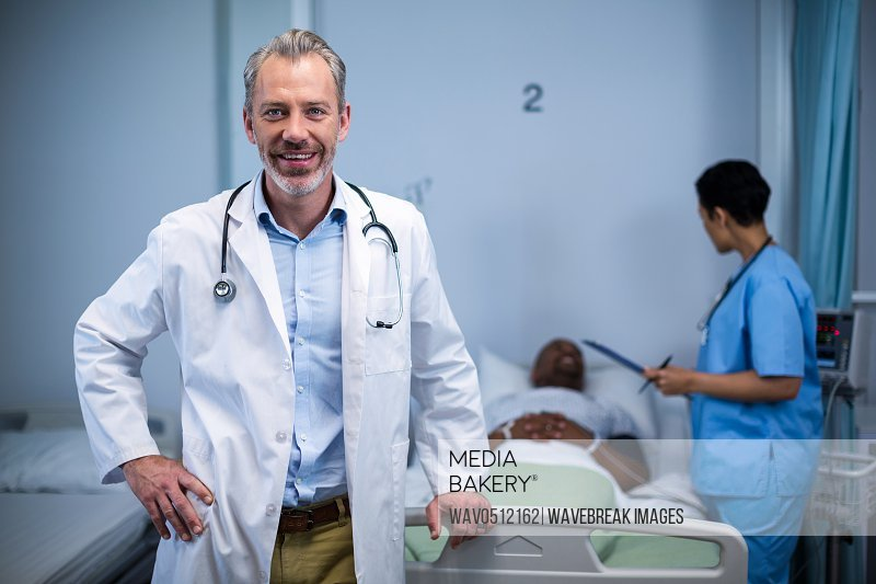 Portrait of doctor standing while nurse consulting patient in background in ward