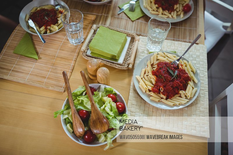 Plates of fresh salads and pasta on dinning table