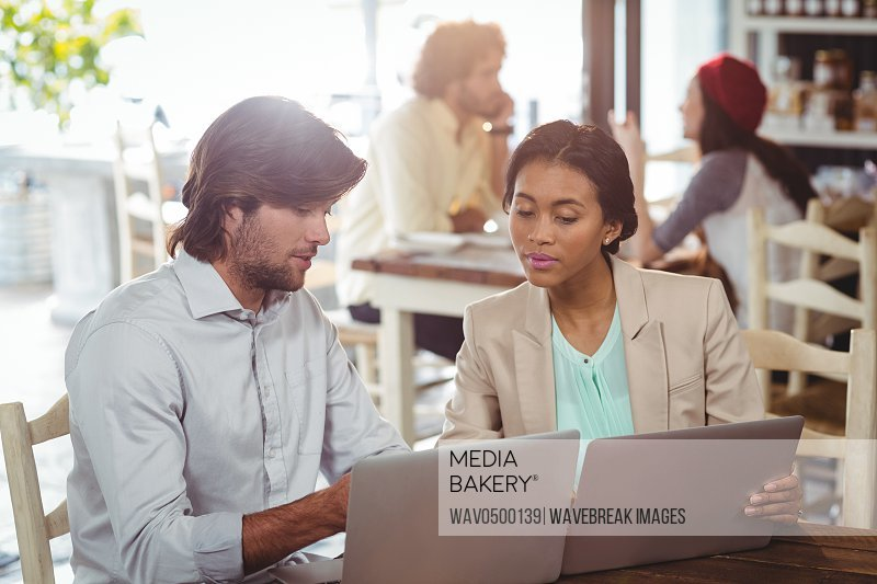 Man and woman using laptop during meeting in cafe