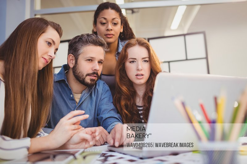 Male coworker with businesswomen using laptop at desk in creative office