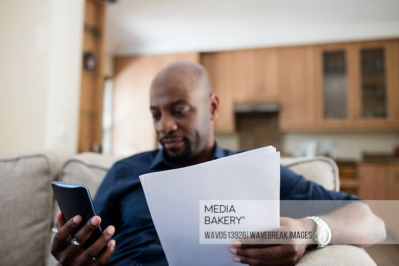 Man holding document while using mobile phone in living room