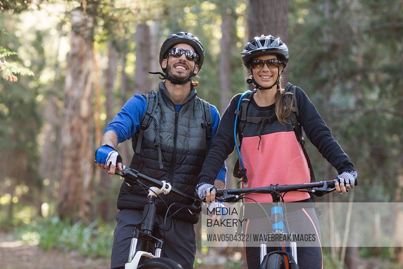 Happy biker couple with mountain bike in countryside