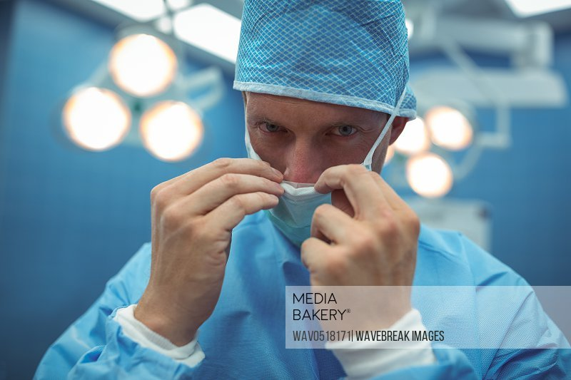 Portrait of male surgeon wearing surgical mask in operation theater