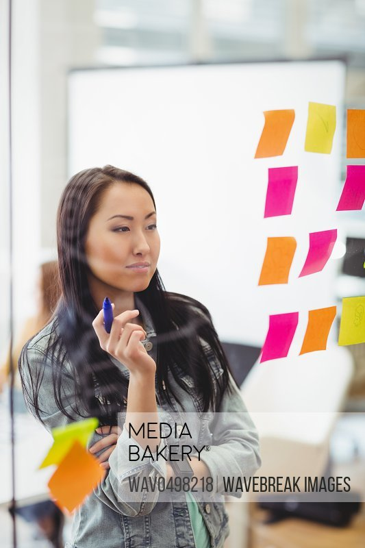 Creative businesswoman looking at multi colored sticky notes on glass in meeting room at creative office