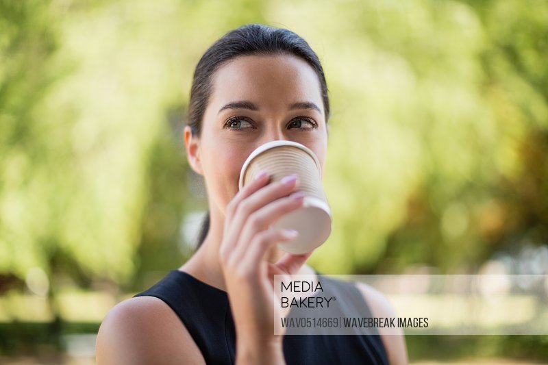 Beautiful woman drinking coffee from disposable cup