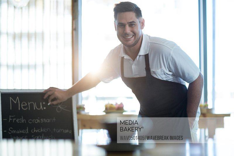 Portrait of smiling waiter writing on menu board in cafe