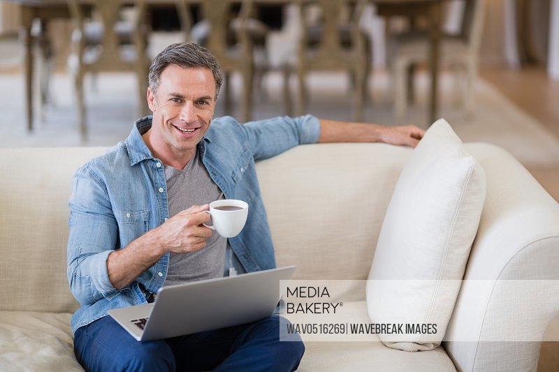 Portrait of smiling man sitting on sofa with laptop having coffee