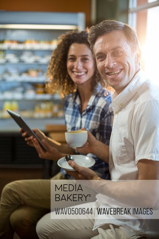 Portrait of man having cup of tea and woman using digital tablet in supermarket