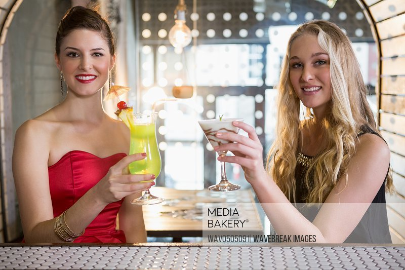 Portrait of smiling female friends holding glass of cocktail in bar