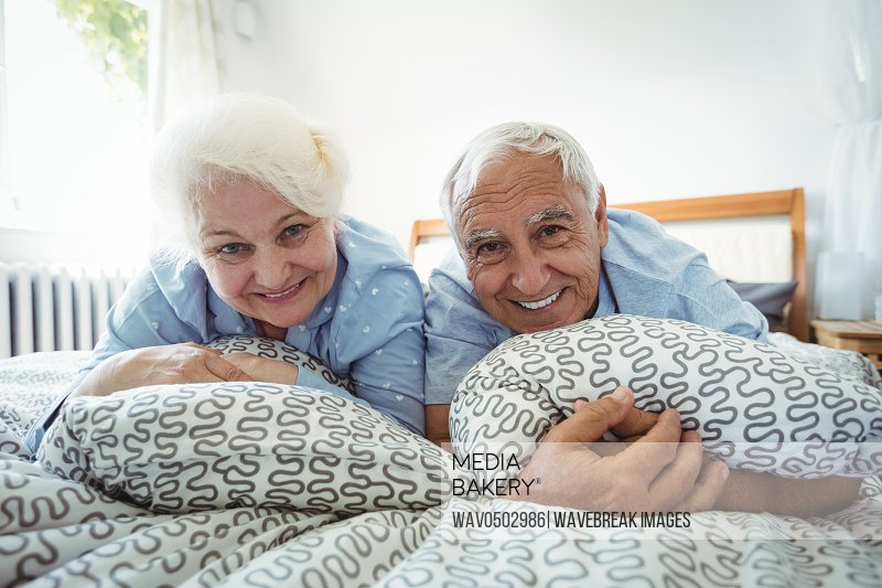 Portrait of senior couple smiling on bed at bedroom