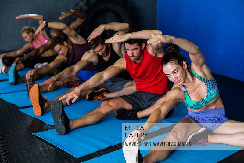 Young athletes doing stretching exercise in gym