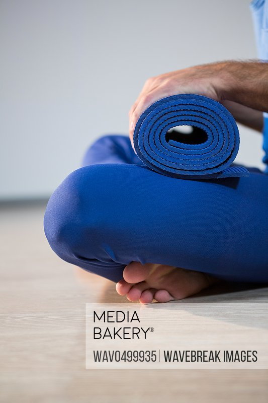 Close-up of man holding exercise mat in gym