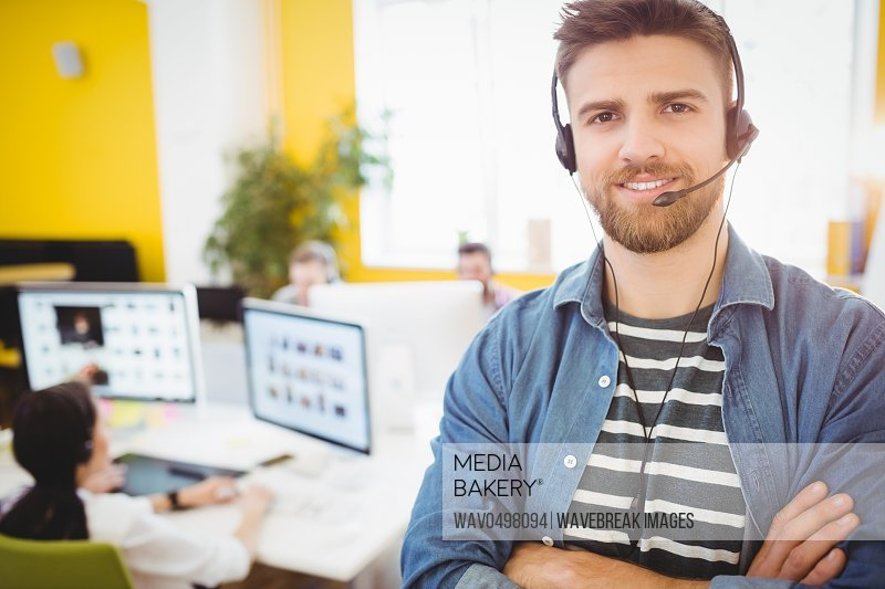 Portrait of happy young male executive wearing headphones at creative office