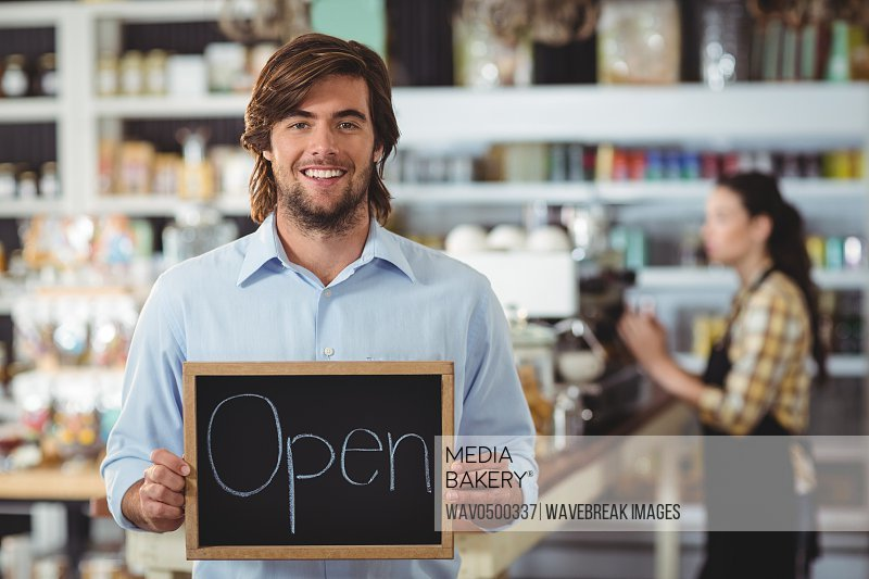 Portrait of waiter showing chalkboard with open sign in cafe