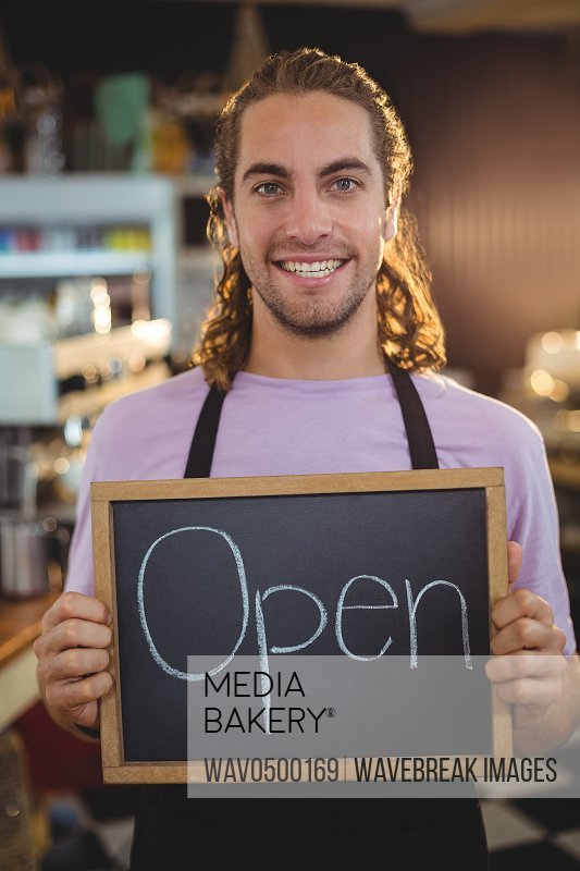 Portrait of smiling waiter holding chalkboard with open sign in cafA?