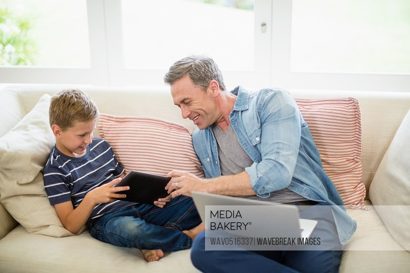 Father and son using laptop and digital tablet in living room