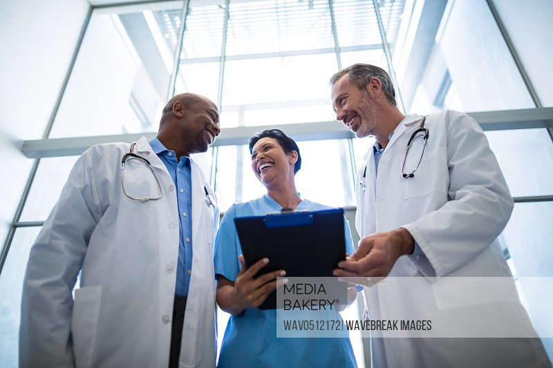 Surgeons and nurse interacting with each other in hospital