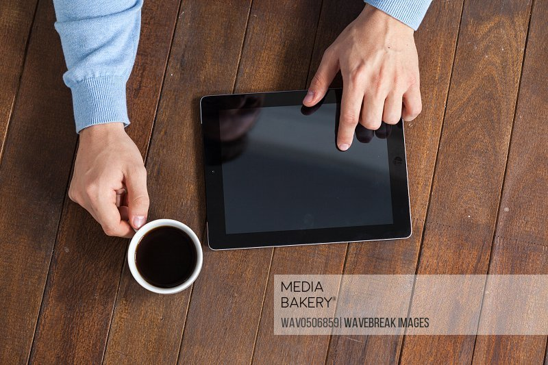 Man using digital tablet while having cup of coffee on wooden table