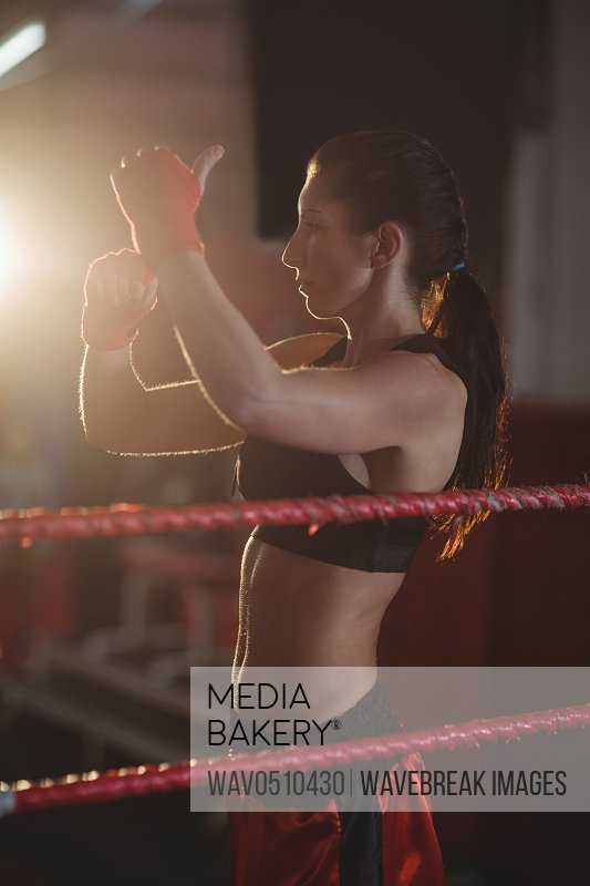 Female boxer wearing red strap on wrist in boxing ring