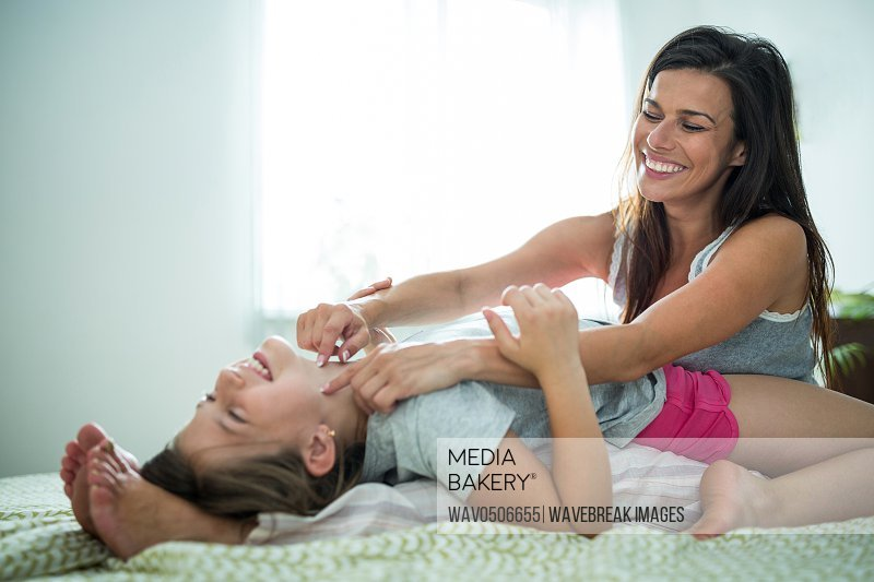 Mother and daughter playing on bed at home