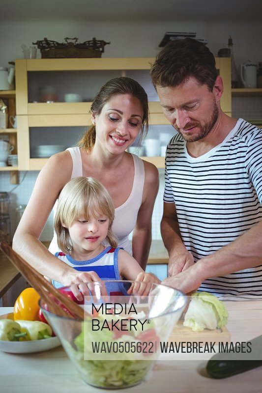 Happy family preparing salad in the kitchen at home