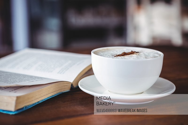 Close-up of coffee cup and book on a table in cafeteria