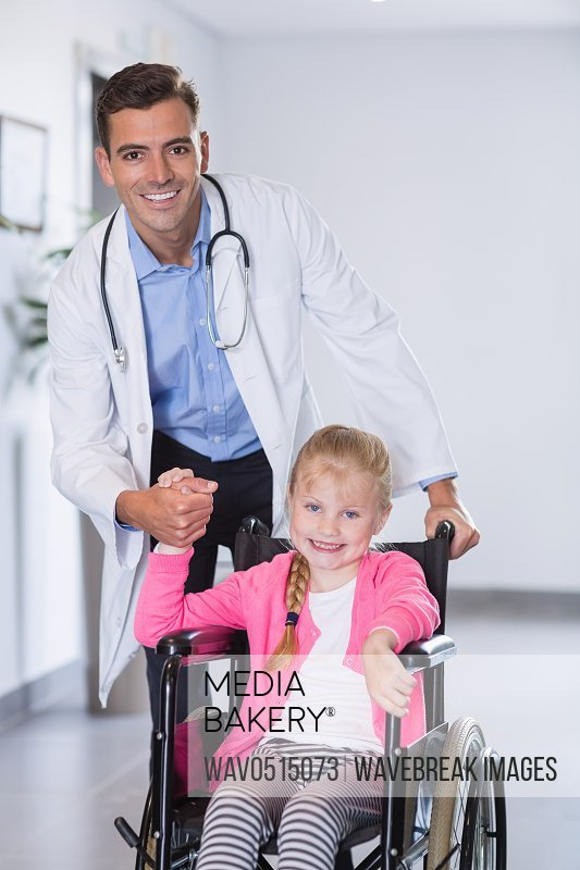 Portrait of doctor pushing girl in wheelchair