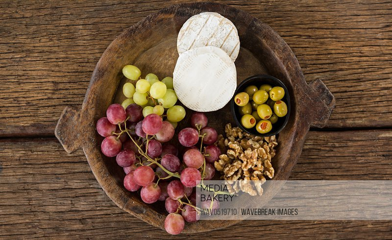Cheese grapes olives and walnut on wooden serving plate