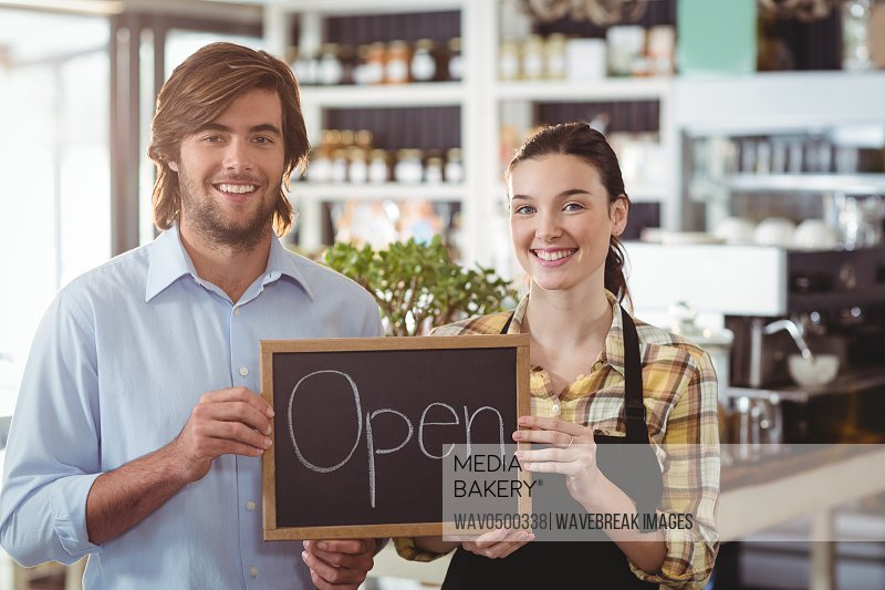 Portrait of man and waitress holding chalkboard with open sign in cafe