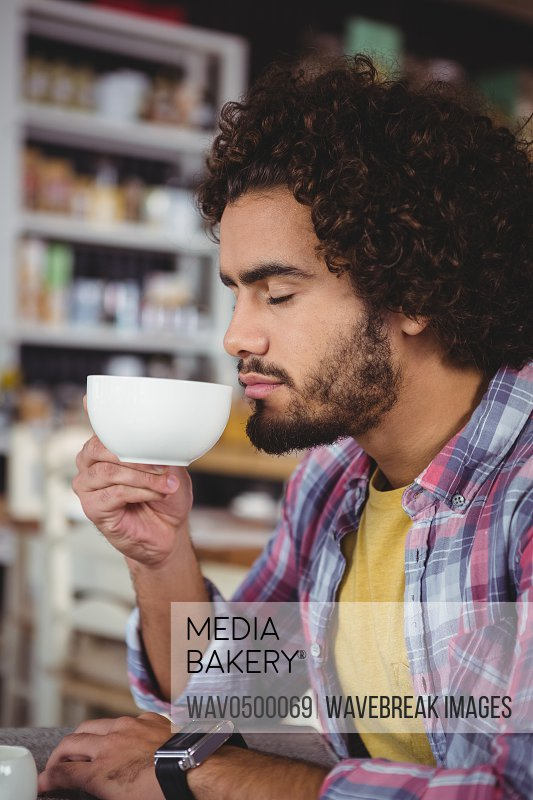 Man having a cup of coffee in cafeteria