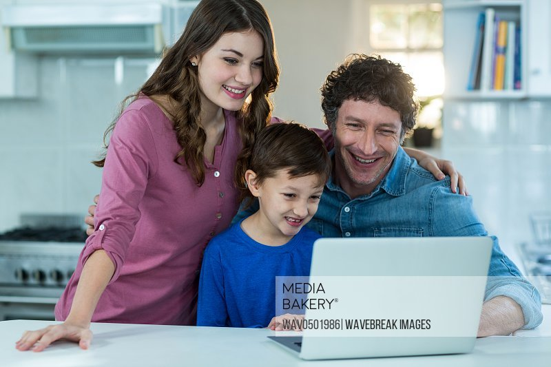 Happy family using laptop at kitchen