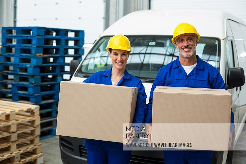 Portrait of delivery workers carrying cardboard box outside the warehouse