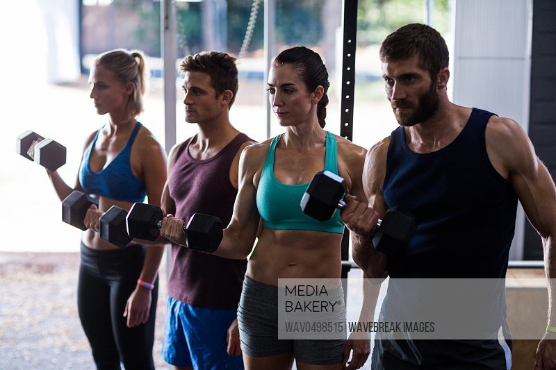 Friends holding dumbbells while working out in gym