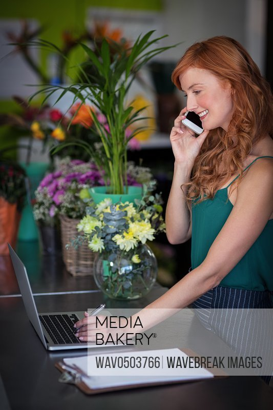 Female florist talking on mobile phone while using laptop in flower shop