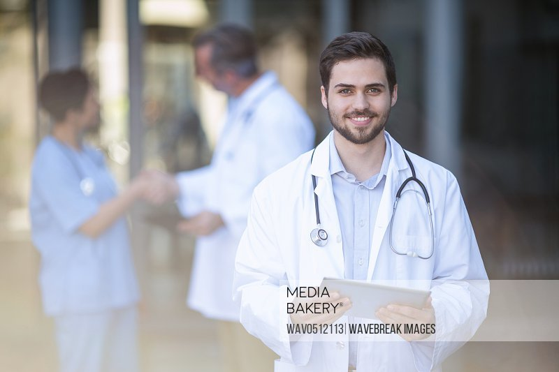 Portrait of smiling doctor standing with digital tablet in hospital
