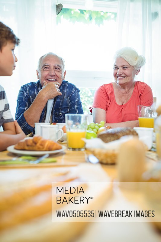 Boy and grandparents sitting at breakfast table at home