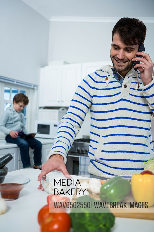Father talking on mobile phone while working in the kitchen at home
